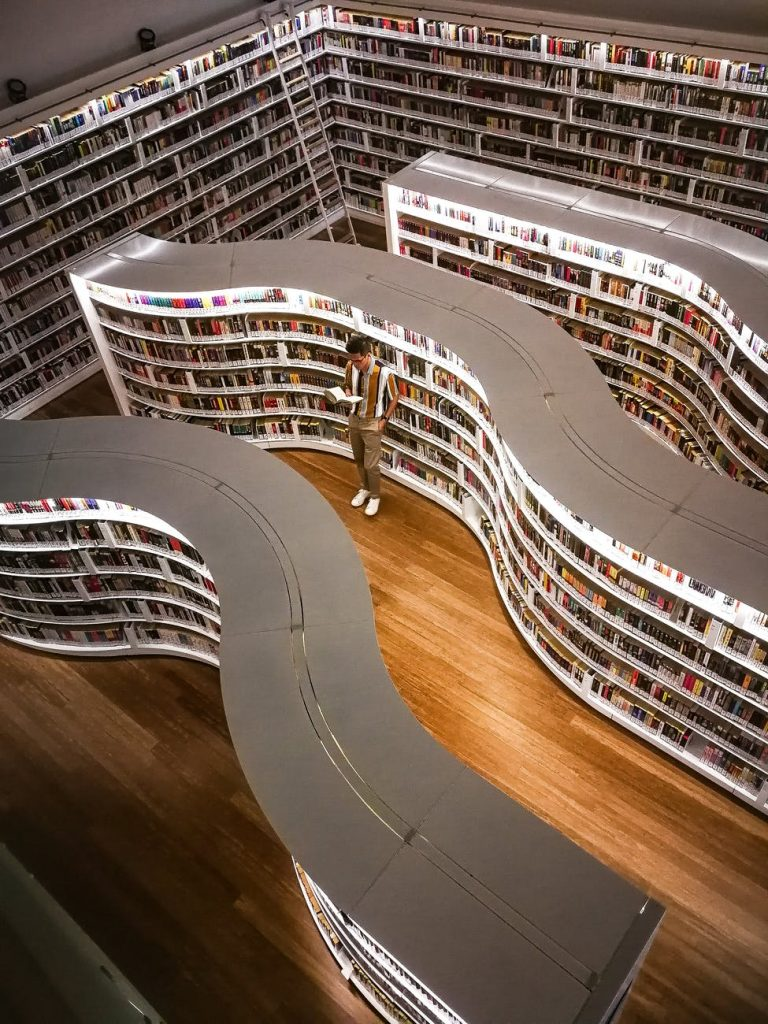 man standing inside library while reading book